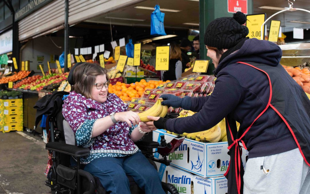 A woman in a wheelchair wearing a purple floral shirt is being passed a bunch of bananas by another lady wearing an apron. In the background there is all sorts of fresh fruits and vegetables, they are at a market.